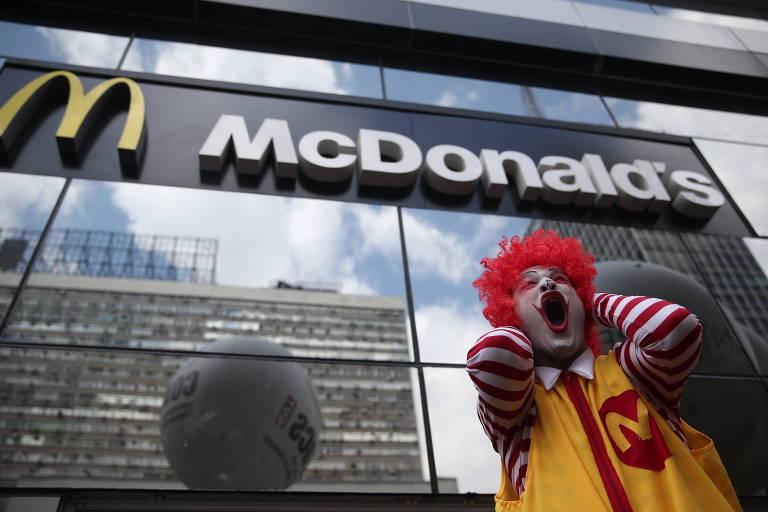 Ronald McDonald grita com as mãos na cabeça em frente a letreiro da empresa