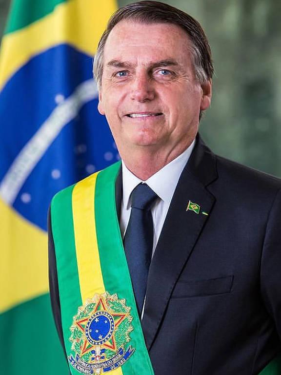 Pelo Instagram, presidente Jair Bolsonaro divulga foto oficial de seu mandato. Ele está de terno azul marinho, vestindo a faixa presidencial verde e amarela. Ao fundo, a bandeira nacional.