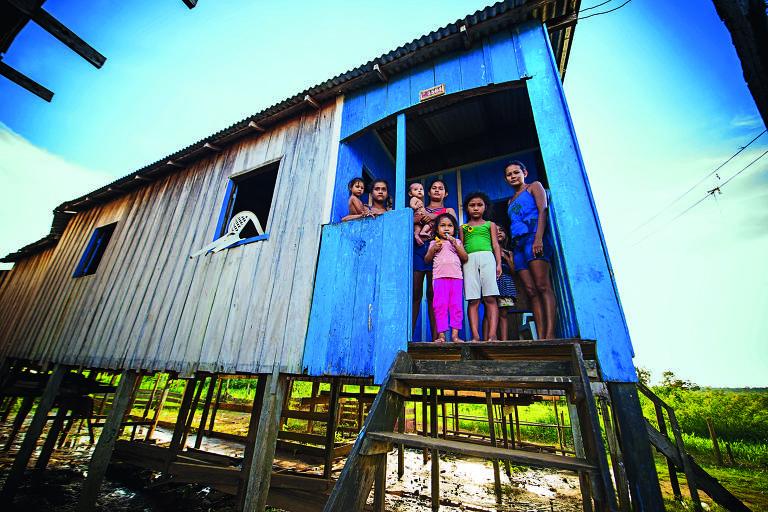 Três jovens mulheres posam para a foto na porta de uma casa sobre uma palafita, de paredes de madeira pintadas de azul e branco. Mais à esquerda a mulher mais nova carrega Larissa, 2. À sua direita, Flávia tem Pedro Lucas, de sete meses, nu, no colo. Ao seu lado, estão outras três crianças e a outra mulher