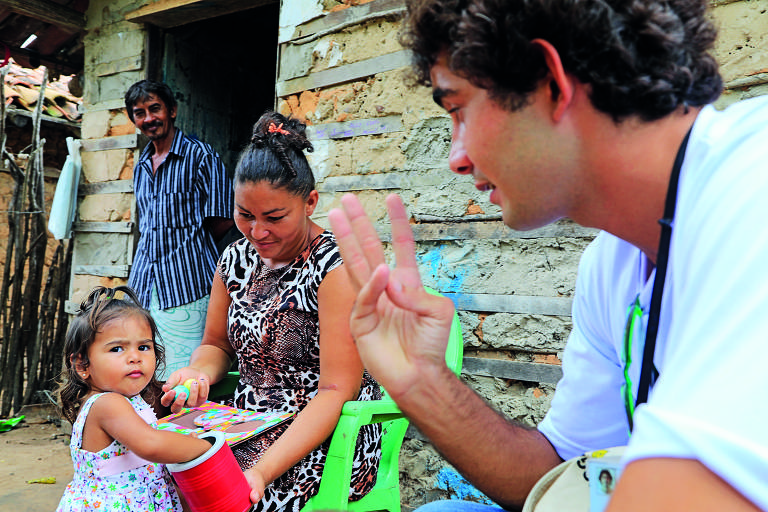 O visitador Felipe Melo conversa com a garota Keylla Sofia, que brinca com um baldinho junto à mãe, que está sentada em uma cadeira de plástico. Ao fundo, o pai de Kylla, Carlos José, observa a cena da porta da casa de paredes rústicas