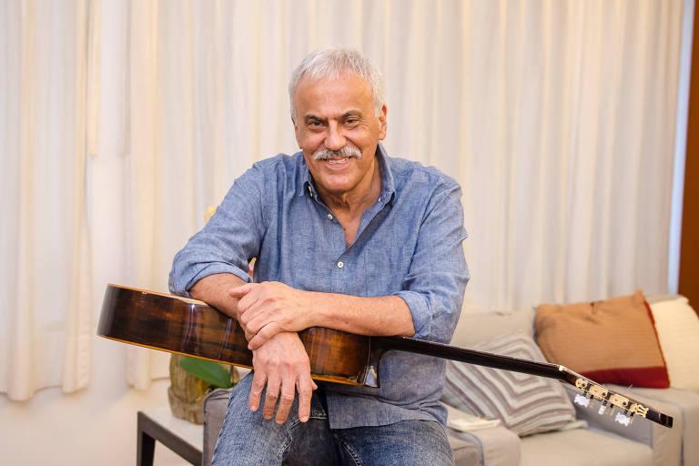 De camisa social na cor jeans, cantor Danilo Caymmi posa sentado, com violão no colo