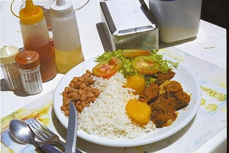 Prato feito em um restaurante do centro de São Paulo, com arroz, feijão, batata, carne e salada, em uma mesa com temperos, garfo e faca, e guardanapo em volta