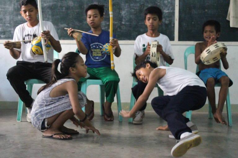 Crianças de bairros pobres de Manila, capital das Filipinas, jogam capoeira e tocam instrumentos típicos em ação de ONG que usa a arte marcial afro-brasileira para reduzir violência