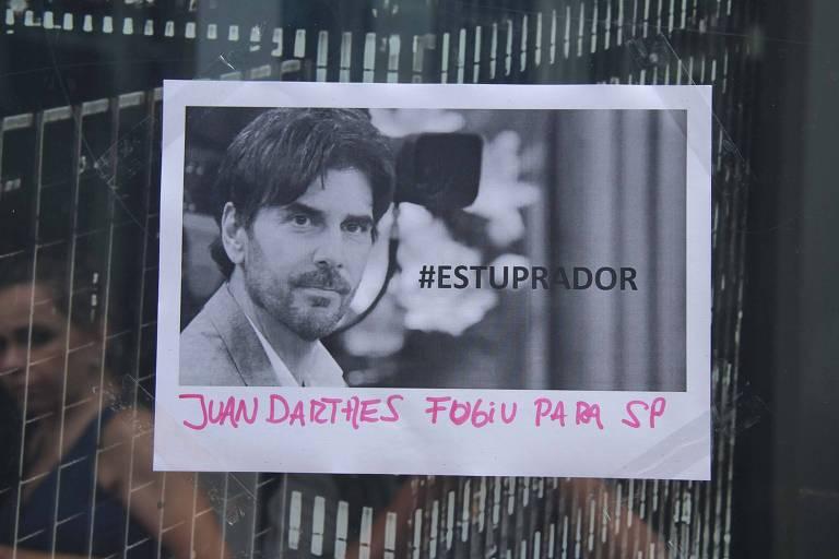 """Facsímile com a foto de Juan Darthés e a palavra """"estuprador"""" colado a porta de vidro"""