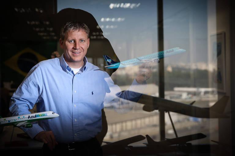 retrato de John rodgerson. o executivo posa para foto atrás de um vidro em que estão refletidas as imagens de duas miniaturas de aviões