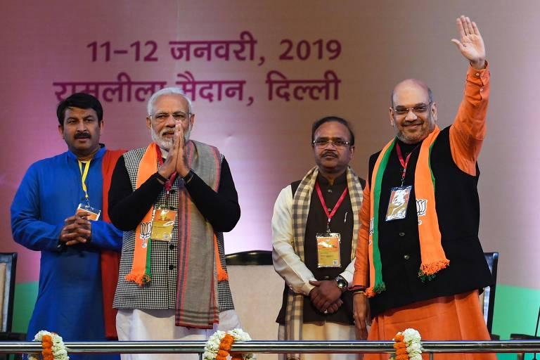 O premiê indiano, Narendra Modi (segundo à esq.), e o líder do seu partido, Amit Shah (acenando), durante convenção do Bharatiya Janata em Nova Déli