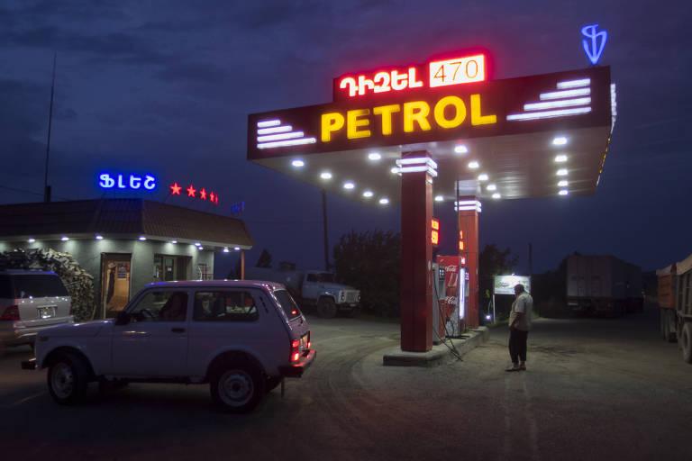Carro em posto de combustível com letreiro luminoso