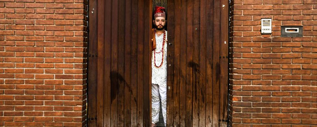 Diego em frente ao portão manchado de óleo