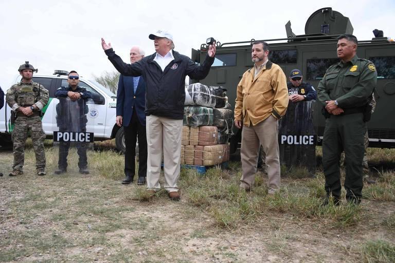 Homens ao lado de veículos da polícia