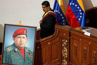 FILE PHOTO: Venezuela's President Nicolas Maduro walks next to a painting of Venezuela's late President Hugo Chavez, during a special session of the National Constituent Assembly to present his annual state of the nation in Caracas