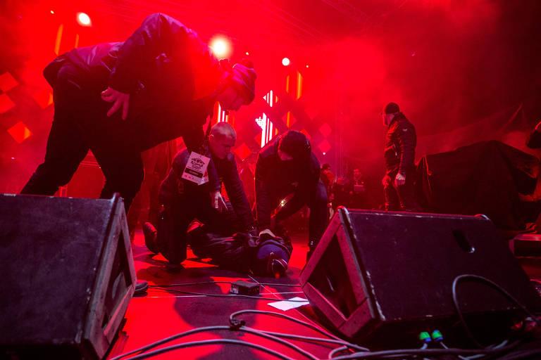 policias seguram homem no chão em palco sob luzes vermelhas