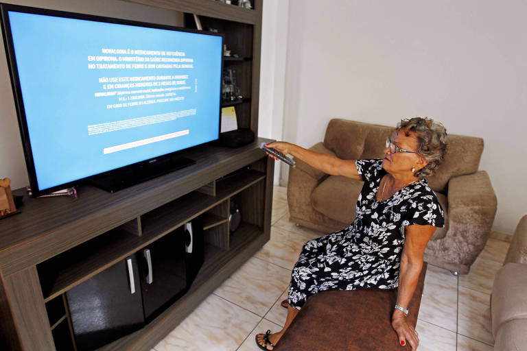 Uma senhora com vestido preto e branco, sentada num sofá, aponta o controle para a televisão