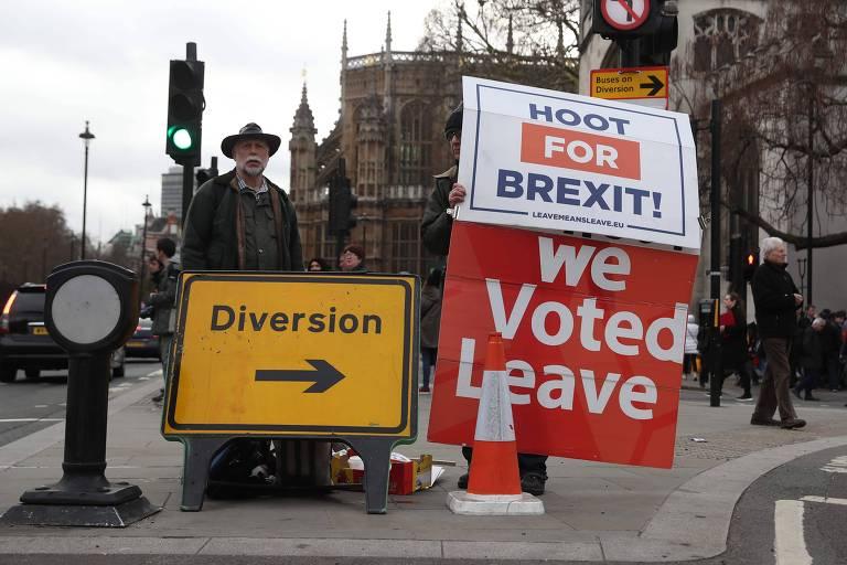 Pessoas favoráveis ao Brexit seguram cartazes em frente ao Parlamento em Londres