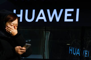 FILE PHOTO: A woman uses her phone as she walks past a Huawei shop in Beijing