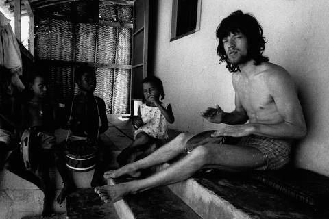 *** ONLINE PAGA*** British musician Mick Jagger (left), from the band the Rolling Stones, plays a hand drum of a beach house as several children join in, Bahia, Brazil, early 1968. (Photo by Adger Cowans/Getty Images) ORG XMIT: 143516867,136640483,143515227