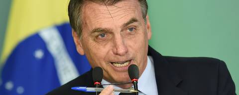 Brazilian President Jair Bolsonaro delivers a speech and shows a popular pen during the signing ceremony of the presidential decree that flexibilizes the possession of firearms, at Planalto Palace in Brasilia, on January 15, 2019. - Bolsonaro decreed the easing of Brazil's gun laws as part of a law-and-order agenda, despite fears it could aggravate already staggering violent crime. Brazil recorded nearly 64,000 homicides in 2017, making it one of the most dangerous countries in the world outside of a war zone. (Photo by EVARISTO SA / AFP) ORG XMIT: ESA072
