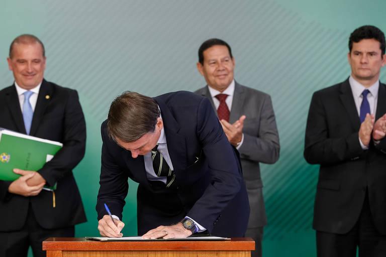 Presidente da República, Jair Bolsonaro, assina decreto para posse de armas, observado pelo chefe da Casa Civil, Onyx Lorenzoni, pelo vice-presidente Mourão e pelo ministro da Justiça, Sergio Moro