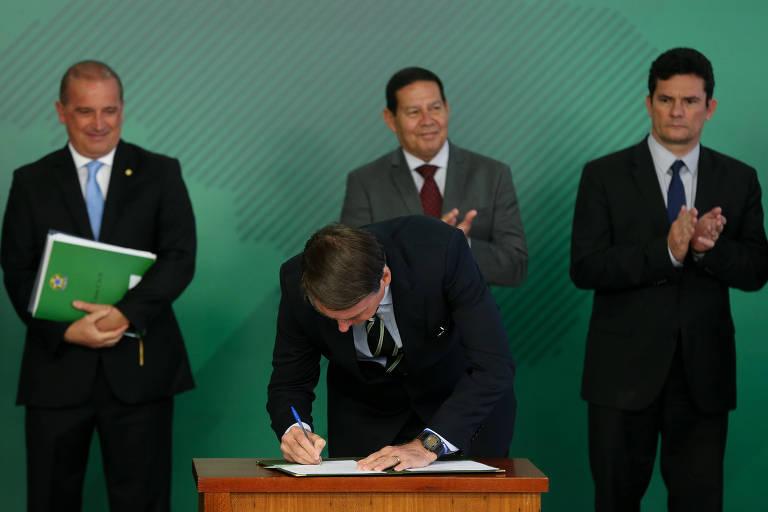 O presidente Jair Bolsonaro assina decreto que modifica a regulamentação para posse de arma de fogo no Brasil
