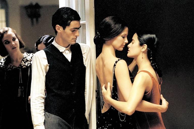 duas mulheres dançam em um salão em frente a um homem e outra mulher, que observam