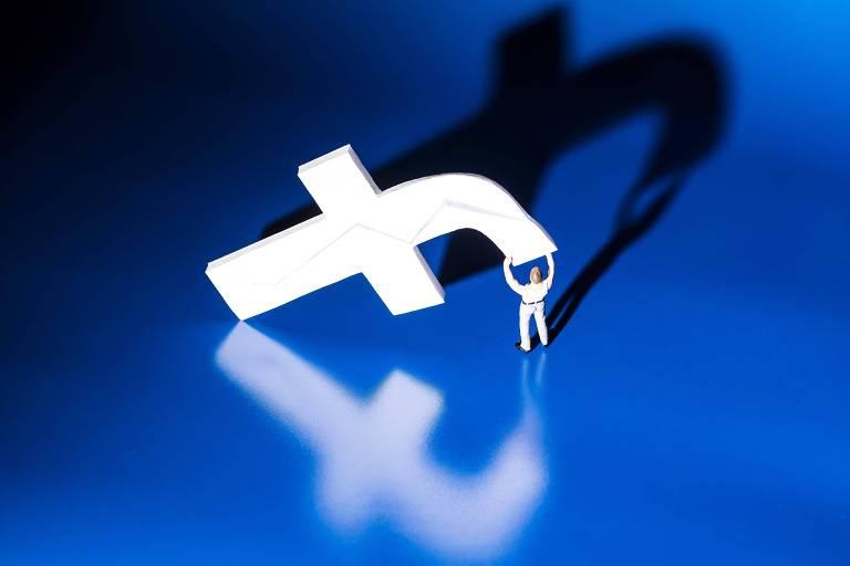 Nesta foto um homem pequeno levanta a letra 'f' do logo do facebook