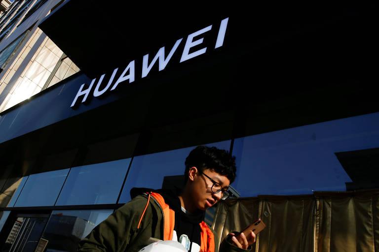 Homem usa smartphone em frente à loja da Huawei em Pequim, na China