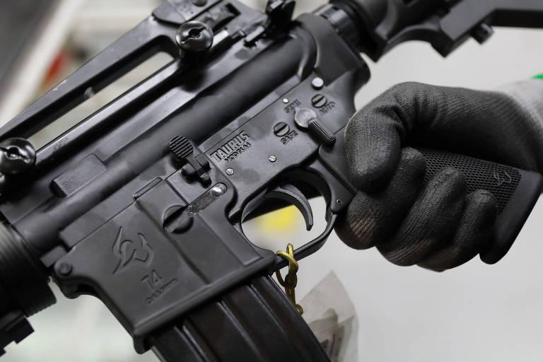 Empregado segura arma da Taurus em fábrica da companhia, em São Leopoldo (RS)