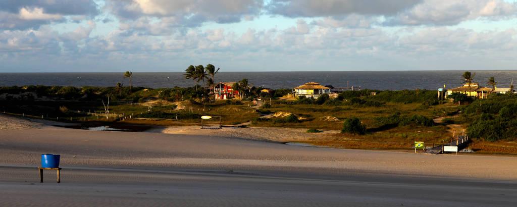 Área de mar com areia e casas em cima de duna, com mar ao fundo