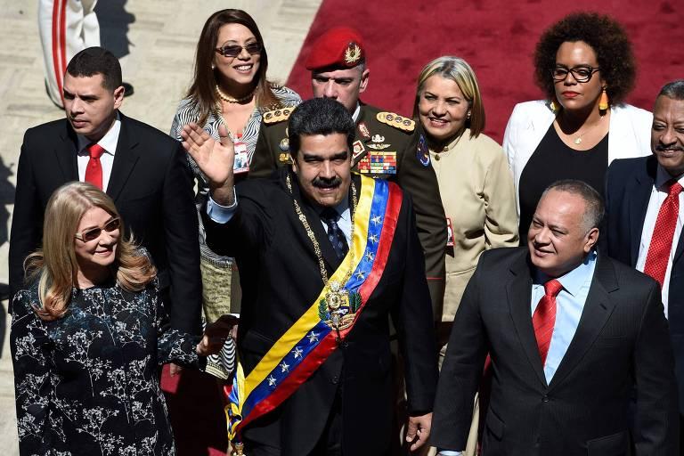 O ditador venezuelano Nicolás Maduro, companhado da mulher Cilia Flores (esq.) e do presidente da Constituinte, Diosdado Cabello (dir) acena antes de evento em Caracas