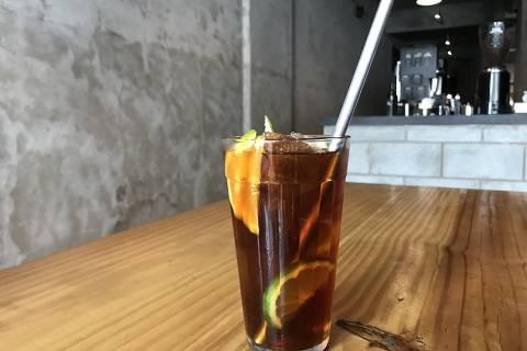 O café gelado com uma rodela de limão e de laranja servido no café Por Uns Dólares a Mais