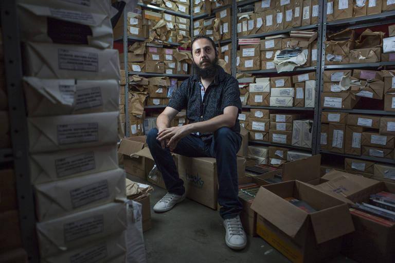 Homem sentado em meio a caixas de papelão