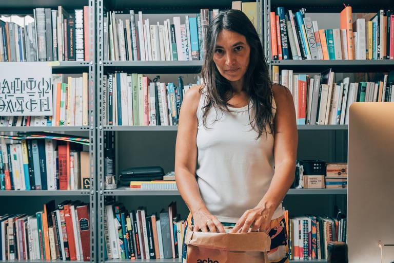 Mulher de camiseta branca em frente a prateleira de livros