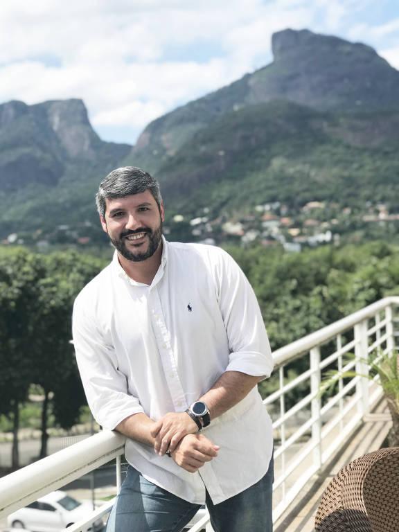 Flávio Osso posa para foto, de camisa branca e calça jeans, apoiado em uma grade de uma varanda. Ao fundo, árvores e morros