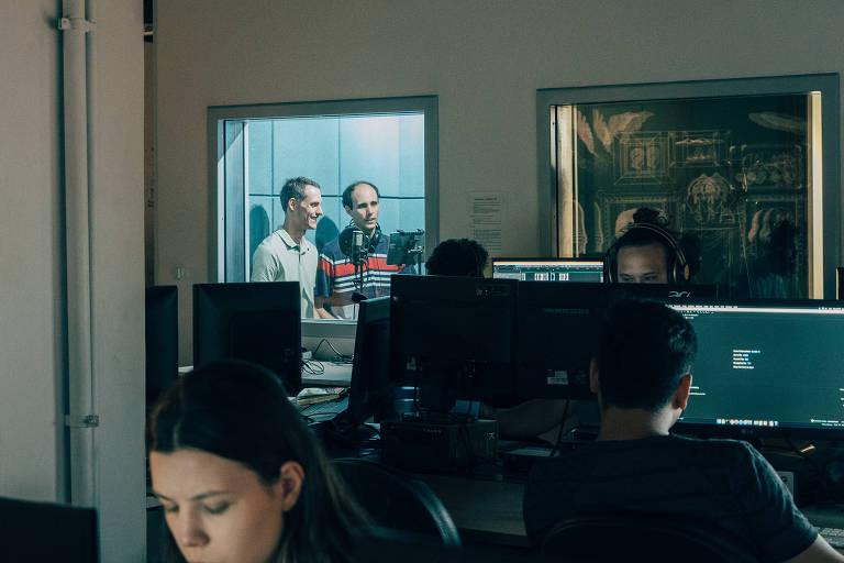 Marcelo e Ricardo podem ser vistos por uma janela dentro de um estúdio de gravação. Do lado de fora, o escritório, com pessoas no computador