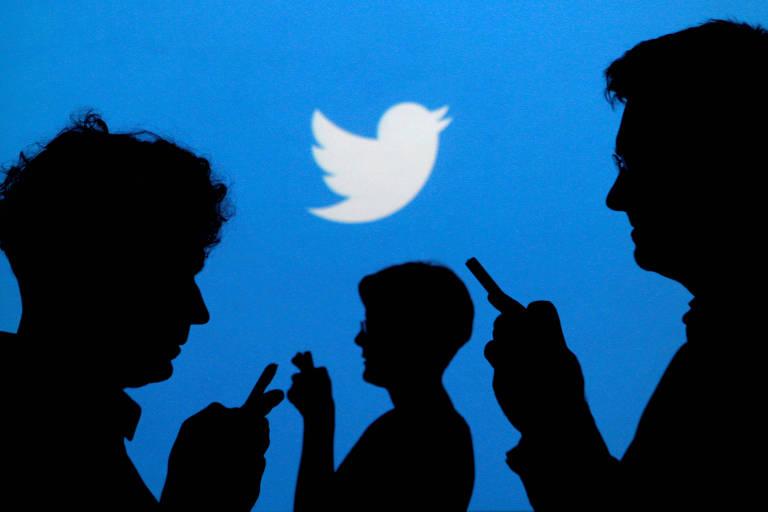Pessoas digitam em seus celulares em frente ao logo do Twitter