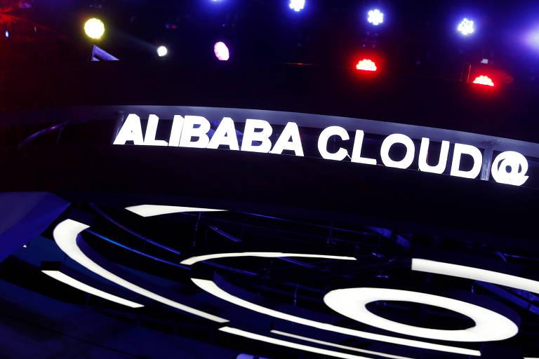 """Luminoso com as palavras """"Alibaba Cloud"""" aparece aceso com algumas luzes coloridas ao fundo e lâmpadas em formato circular logo abaixo"""