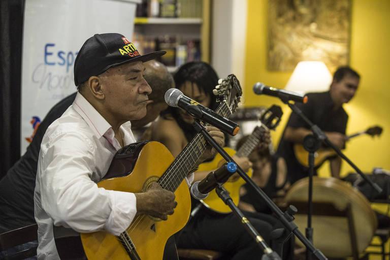 Homem de camisa branca e boné preto tocando violão e cantando