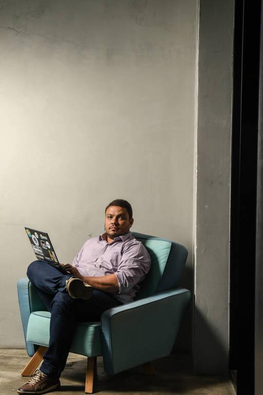 Homem sentado em poltrona azul com notebook no colo