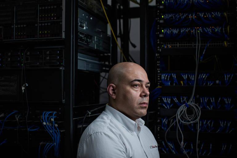 Homem careca de camisa branca contra fundo preto, com cabos de equipamentos