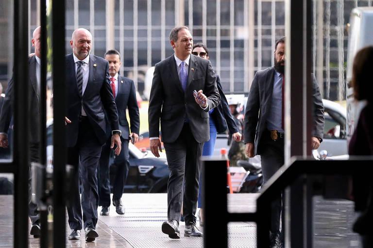 Miguel Ángel Martin, presidente da Suprema Corte da Venezuela, se aproxima de porta de imóvel em Brasília, no ano passado; a seu lado, outros homens de terno e gravata
