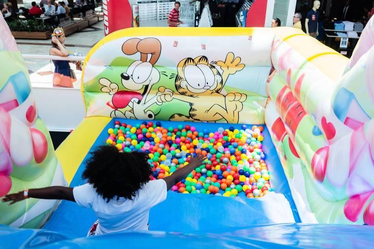 Criança se diverte em escorregador que desemboca em uma piscina de bolinhas, no Parque Garfield