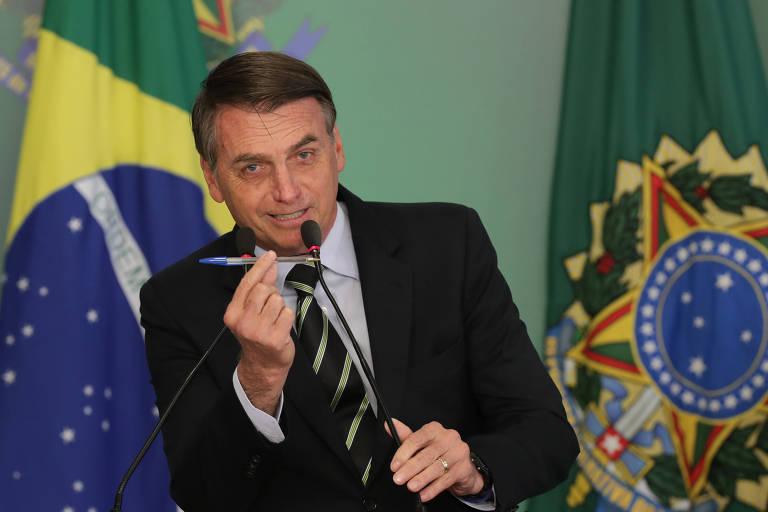Bolsonaro segura caneta na mão antes de assinar decreto