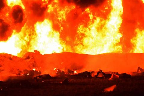 TOPSHOT - EDITORS NOTE: Graphic content / The fire is raging behind the bodies of burned victims at the scene of a massive blaze trigerred by a leaky pipeline in Tlahuelilpan, Hidalgo state, on January 19, 2019. - A leaking fuel pipeline triggered a massive blaze in central Mexico, killing at least 20 people and injuring another 54, officials said. Omar Fayad, governor of Hidalgo state, said locals at the site of the leak were scrambling to steal some of the leaking oil when at least 20 of them were burned to death. (Photo by Francisco Villeda / AFP) ORG XMIT: 738