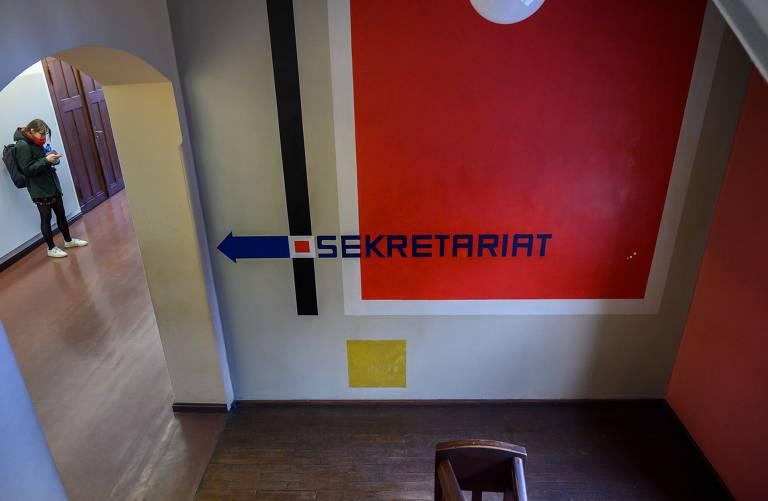 Parede em corredor da universidades mostra uma seta horizontal azul indicando caminho à esquerda para a secretaria; há também uma faixa preta, um quadrado vermelho e uma quadrado menor amarelo nesta parede