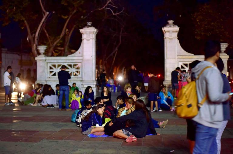 pessoas estão sentadas no chão ao ar livre