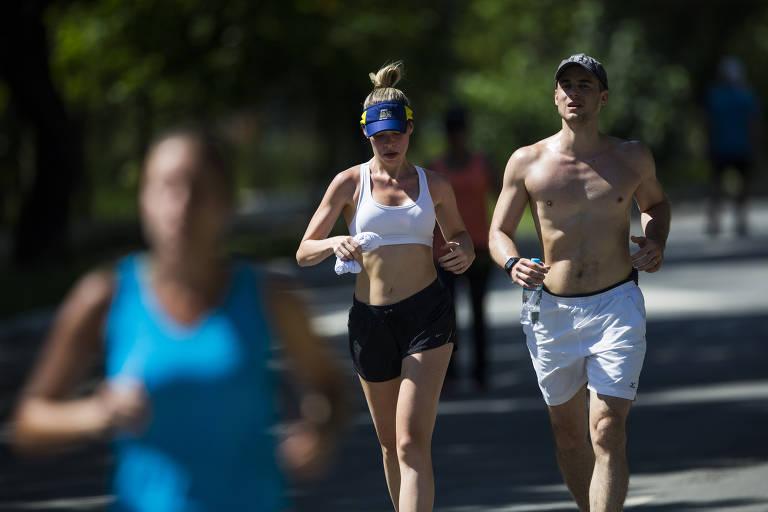 Sob sol forte, loira usa viseira, top e shorts para correr ao lado de homem sem camisa, com shorts branco e boné