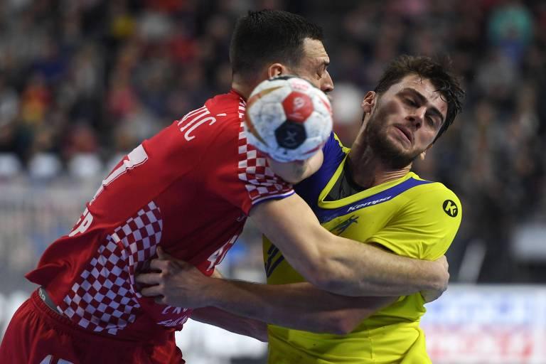 Haniel, com camisa amarela e azul da seleção e cara de dor, é agarrado por atleta com camisa vermelha e branca da Croácia