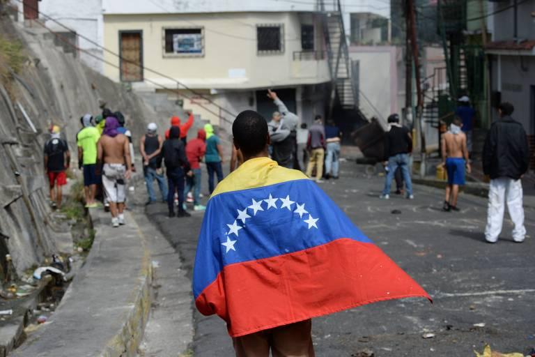 Manifestante embrulhado em bandeira da Venezuela protesta contra o governo em Cotiza nesta segunda
