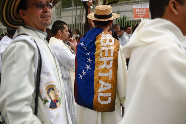 """Padre envolto em bandeira venezuelana com a palavra """"Liberdade"""" em Caracas"""