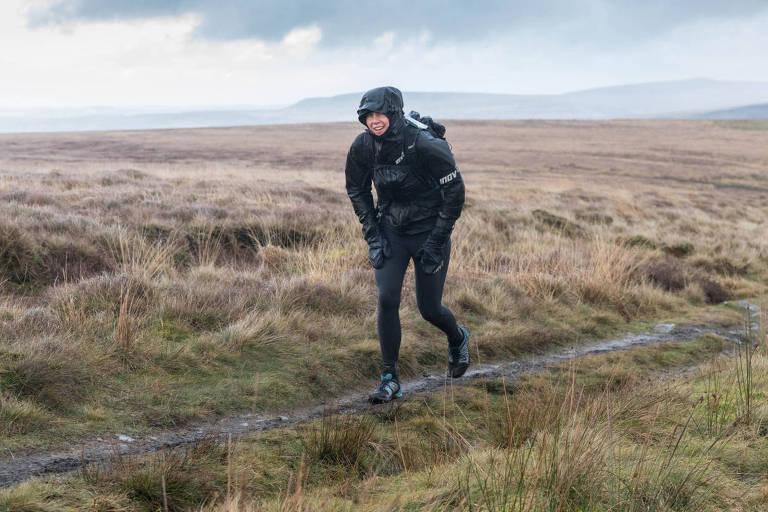 Mulher vestindo roupa de ginástica preta, casaco com capuz e mochila corre em uma trilha em uma paisagem rural, com vegetação baixa