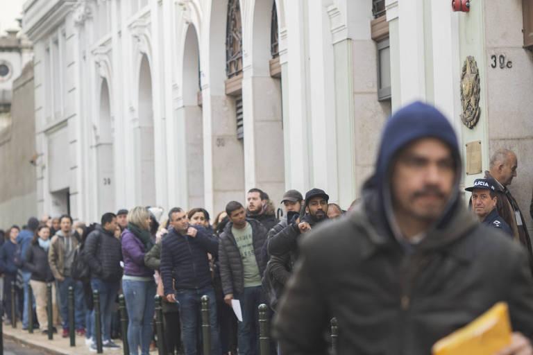 fila de pessoas na frente de um edifício com arquitetura típica portuguesa